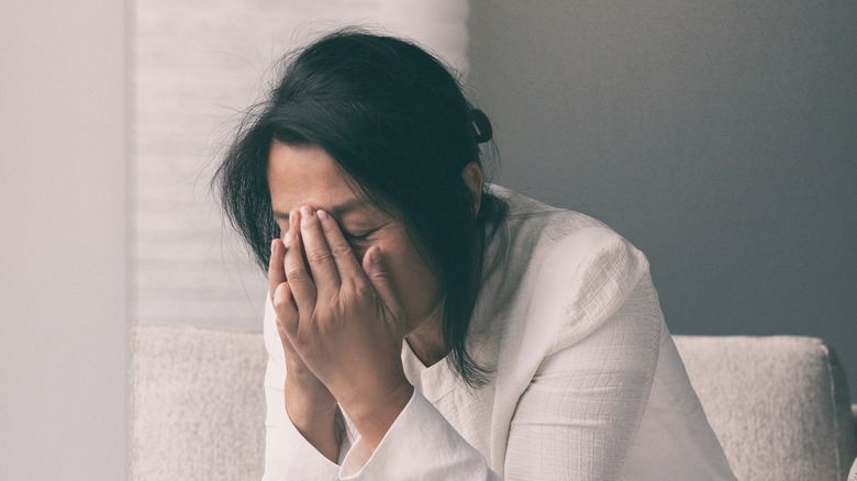 A woman with a headache holding her face in pain