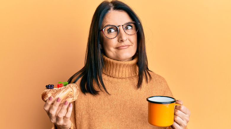 A woman holding pastry and mug