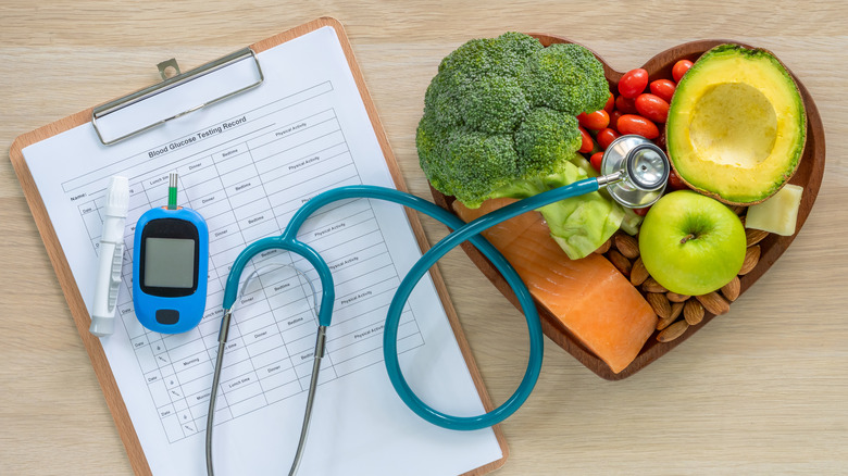 heart-shaped plate of food next to glucose monitor and record sheet