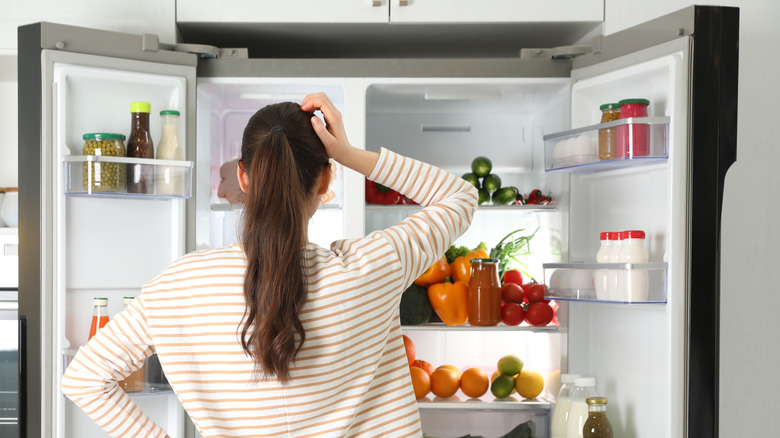 woman looking at contents of refrigerator