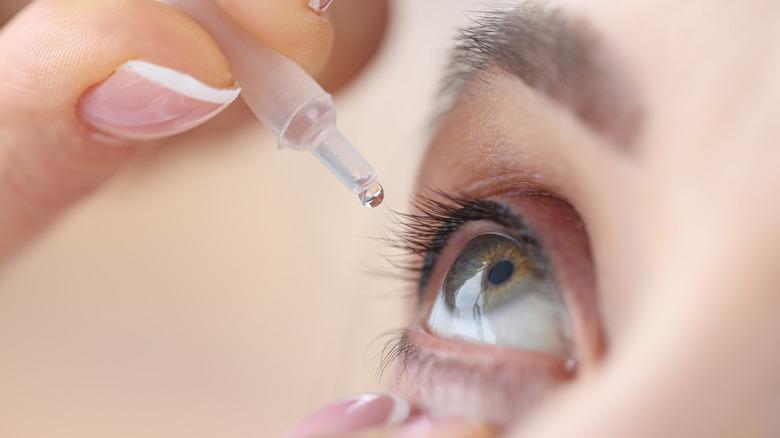 Someone puts eye drops in their eye
