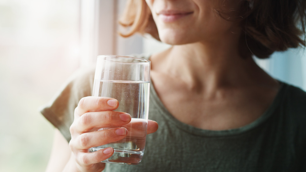 woman holding water glass