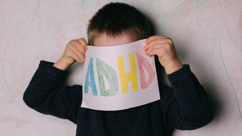 Child holding sign saying ADHD