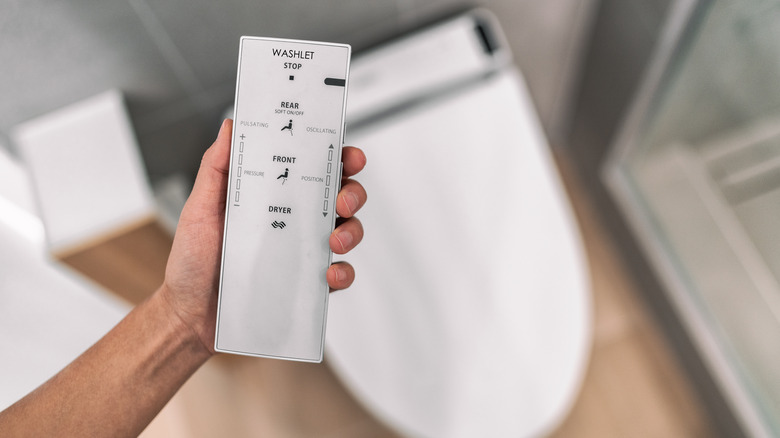 Close up of a hand holding a bidet remote with bidet in background