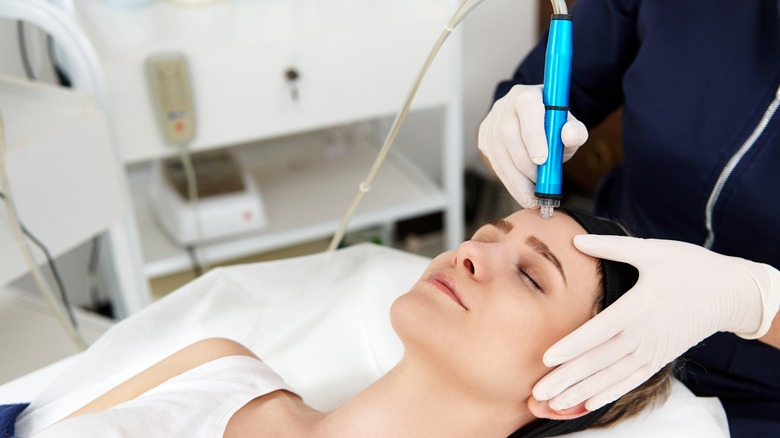 A doctor uses a pore vacuum on a woman's face