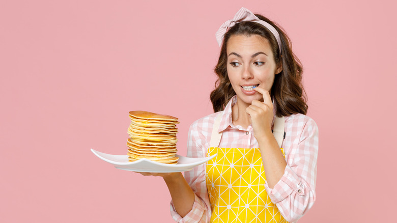 woman holds plate of pancakes