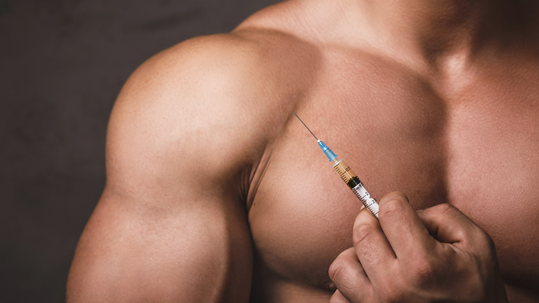 muscular man holding a syringe