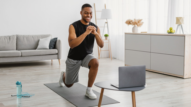 A man performs lunges at home
