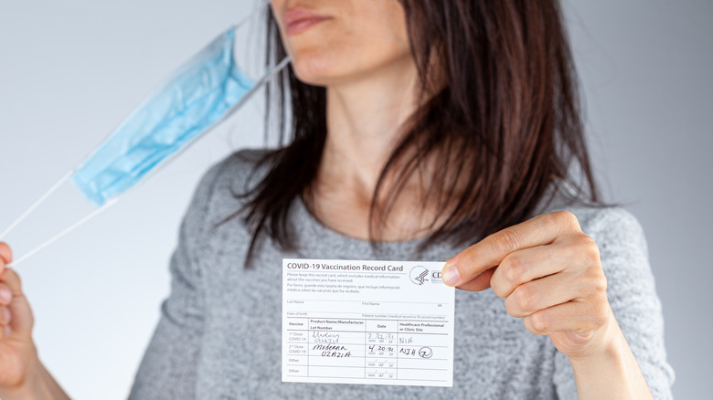 woman taking off mask, showing vaccination card with two doses