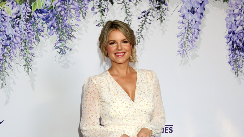 Ali Fedotowsky poses for a photo in front of a white and purple backdrop