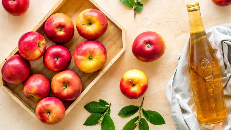 apples in box with bottle of vinegar on dish towel