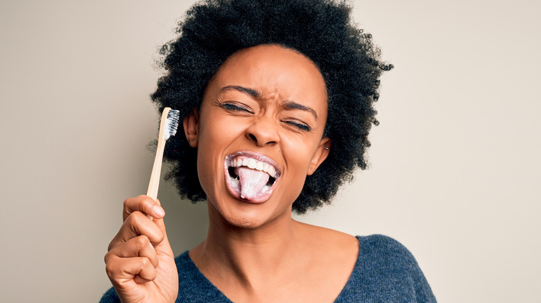Woman brushing her teeth and tongue with toothbrush and toothpaste