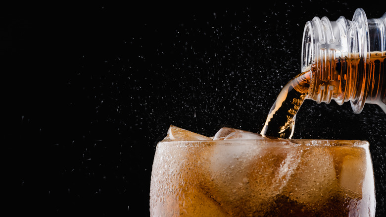 fizzy diet soda being poured into a glass with ice