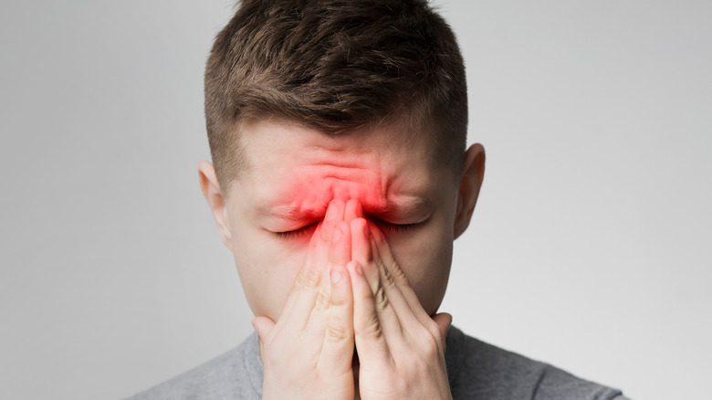 Man suffering from sinus pressure, touching his nose with closed eyes
