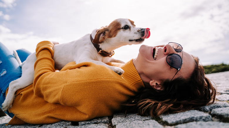 Woman laughing with her dog on her