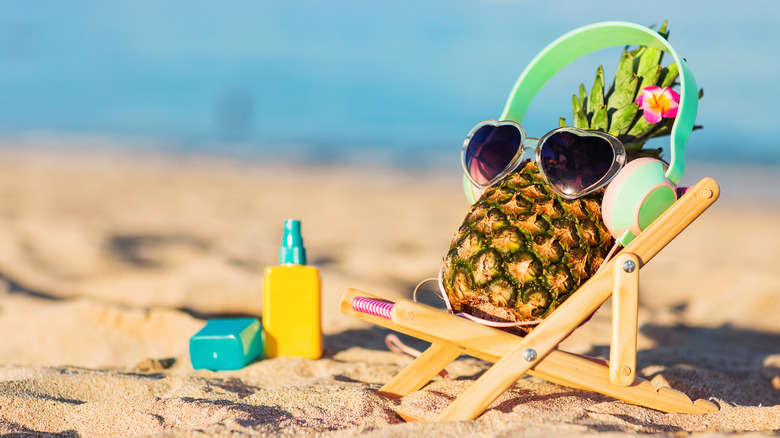 A pineapple with sunglasses and headphones reclining in a miniature lounge chair on a beach