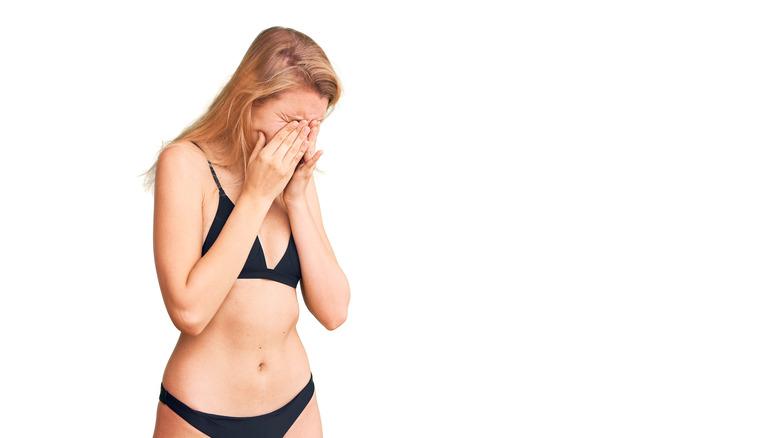 woman in bikini rubbing her eyes