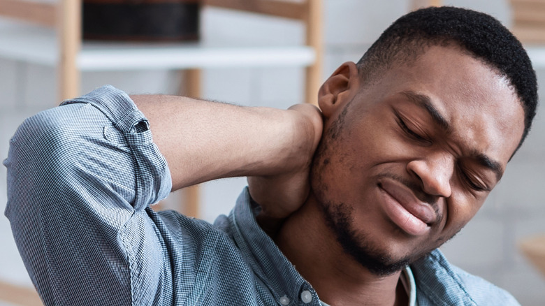 Man holding neck with painful face