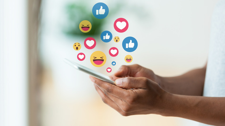 Close up of a person's hands as they hold a phone with reaction icons floating above the screen
