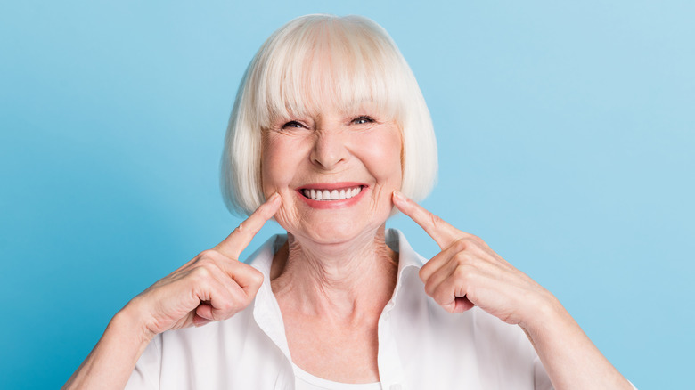 senior woman smiling and pointing at teeth