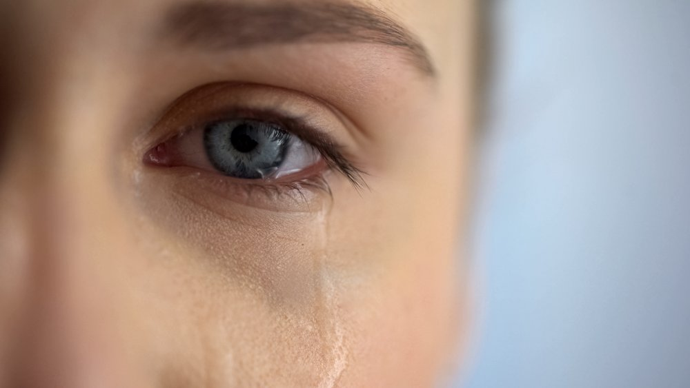 Tears falling from a blue eye
