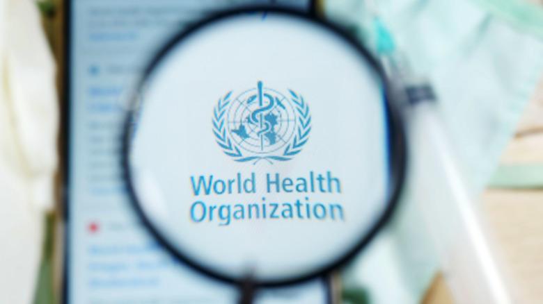 WHO (World Health Organization) logo under magnifying glass