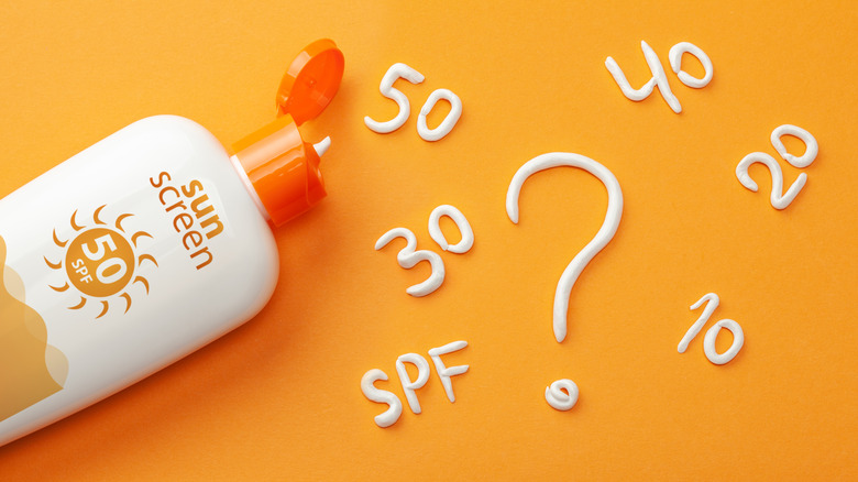 bottle of sunscreen with various SPFs on background