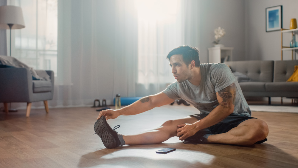 man does stretch in living room