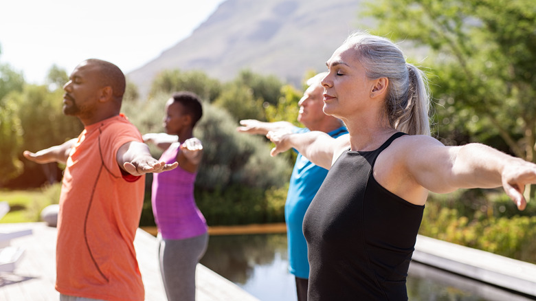 A group of people with their arms out as they exercise