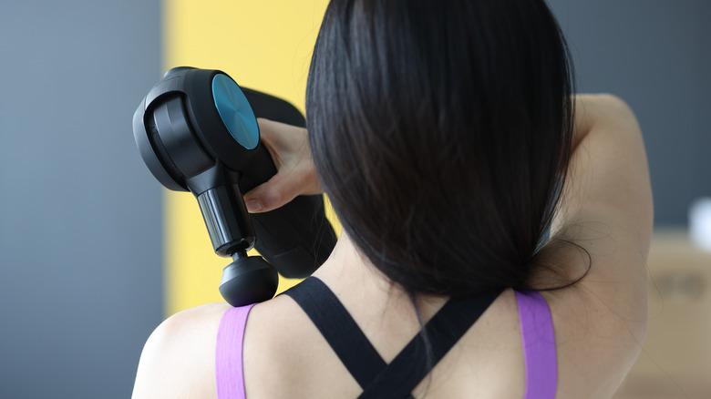 Woman holding massage gun