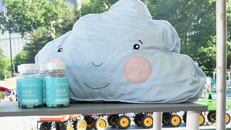 Several bottles of SugarBearHair vitamins next to a cloud pillow