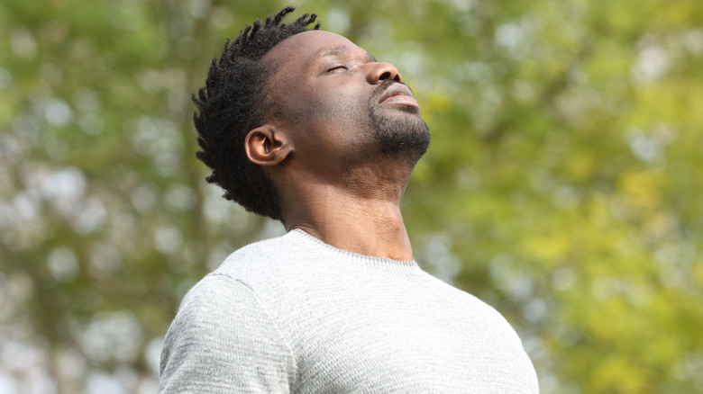 Man breathing deeply outdoors