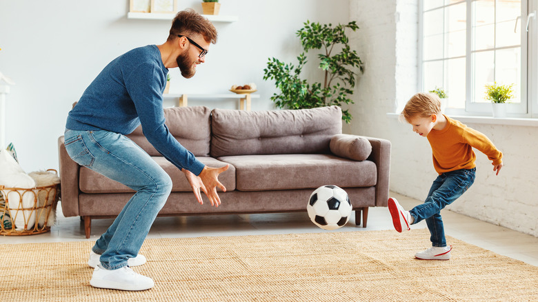Adult and child playing soccer in a living room