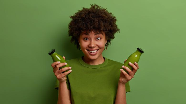 Girl holding bottles of green juice
