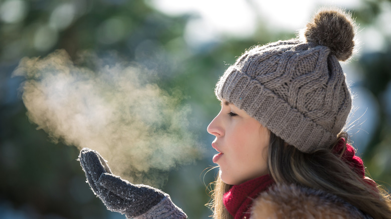 woman wearing hat and blowing out breath in cold outdoors