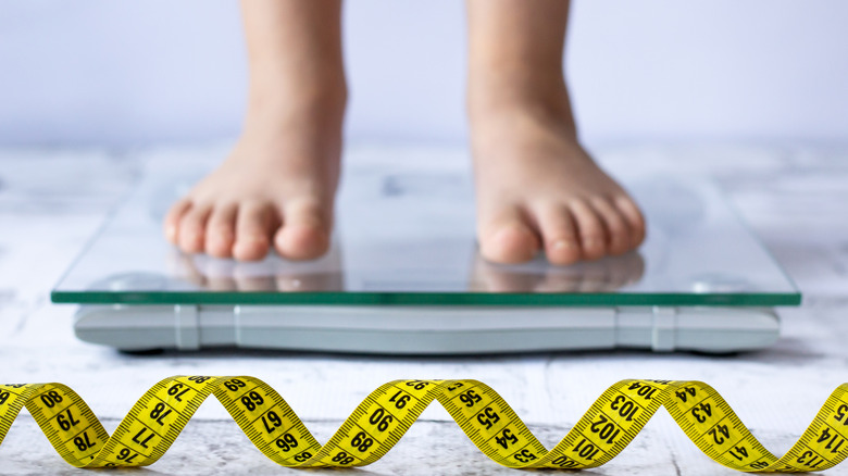 a child's feet on a scale with a measuring tape in front