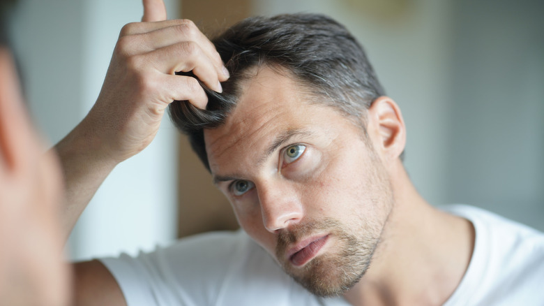A man looks at his hair in the mirror
