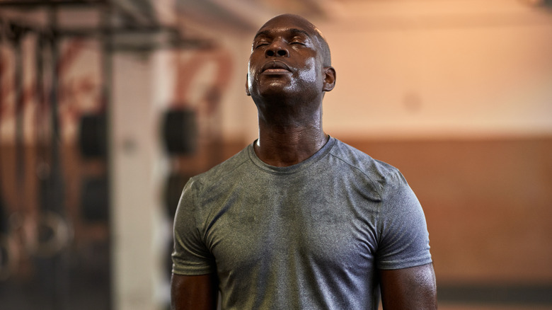A man wearing a grey T-shirt sweating at the gym