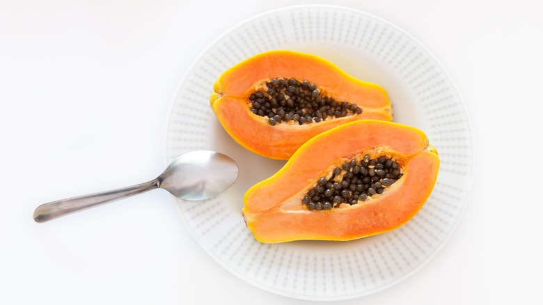 A papaya is cut open on a plate next to a spoon