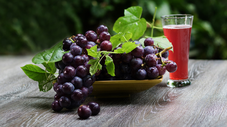 grapes on table with a glass of grape juice