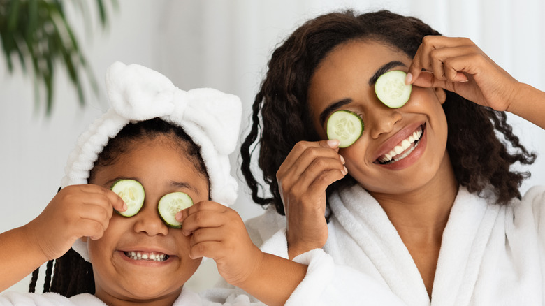 mother and daughter in white robes holding cucumbers to their eyes
