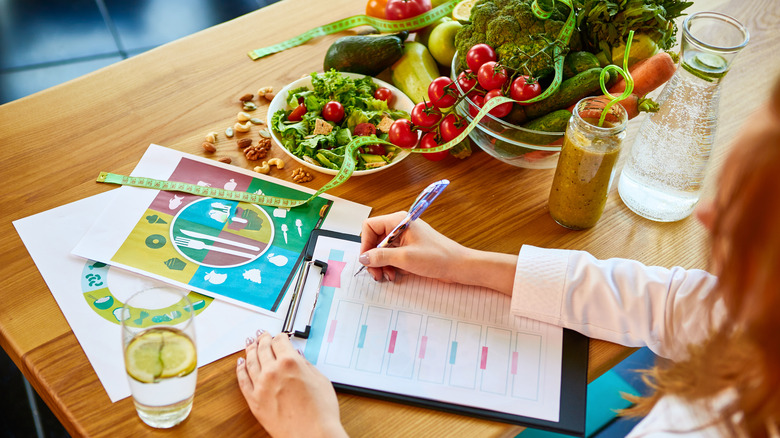 Woman dietitian in medical uniform with tape measure working on a diet plan sitting with different healthy food ingredients in the green office on background. Weight loss and right nutrition concept. Reverse dieting.
