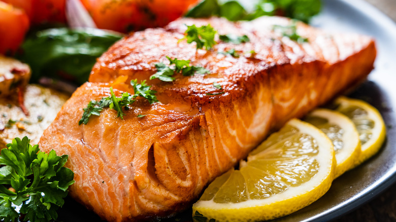 a piece of grilled salmon on a plate with lemon slices
