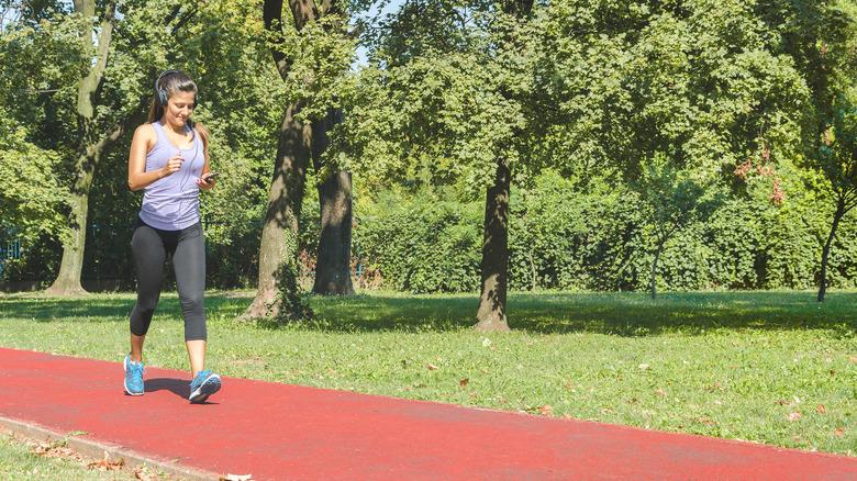 A woman walks briskly on a track