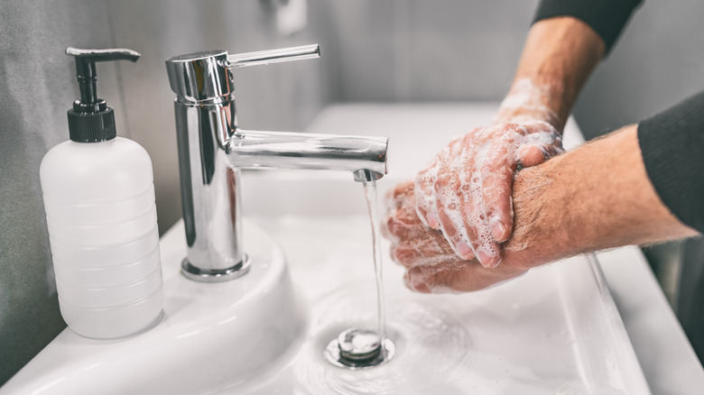 Man washing h ands in sink