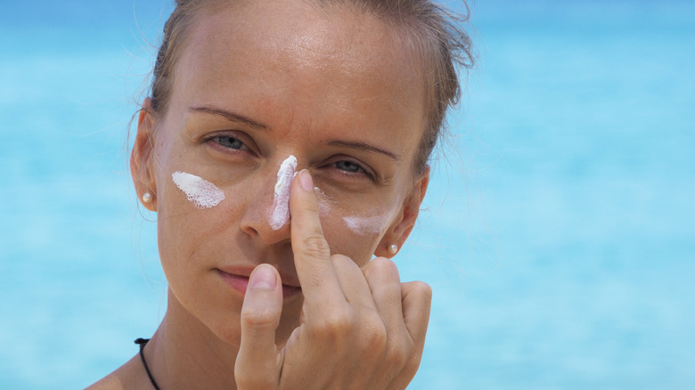 Woman applying sunscreen to face