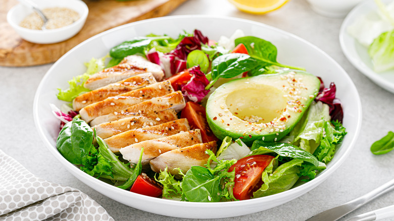 A grilled chicken salad with avocado