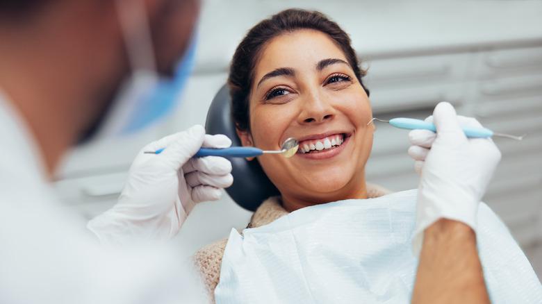 A woman smiles in a dentist chair