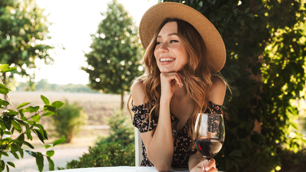 Smiling woman outside holding a glass of red wine
