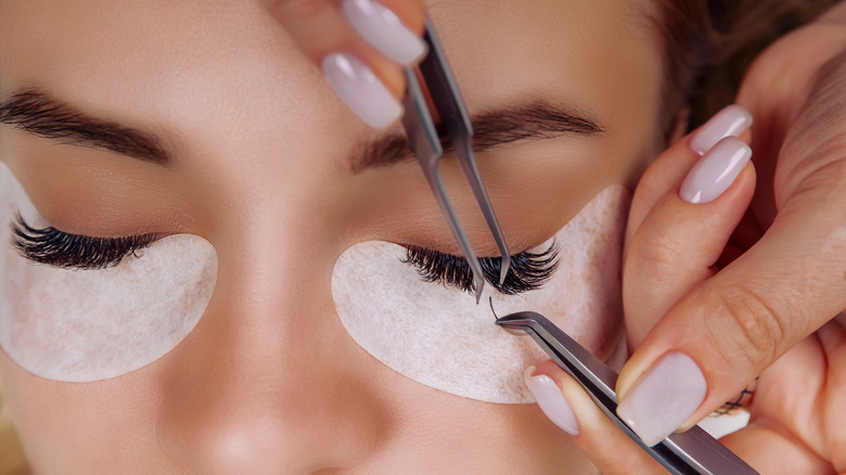 A closeup of a woman getting eyelash extensions